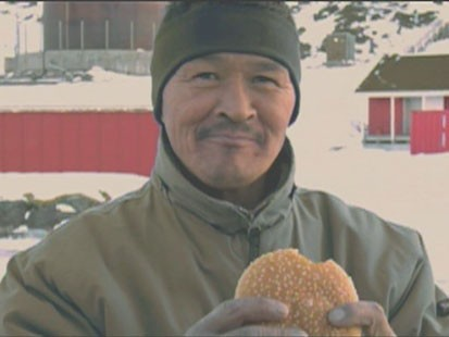 A picture of a man holding a hamburger.