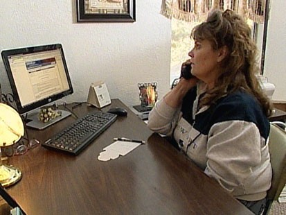VIDEO: A woman on the phone at a desk.