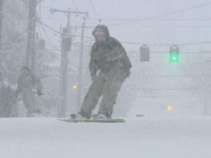 VIDEO: Someone snowboarding down a street.