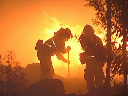 A Picture of two fire fighters in front of flames.