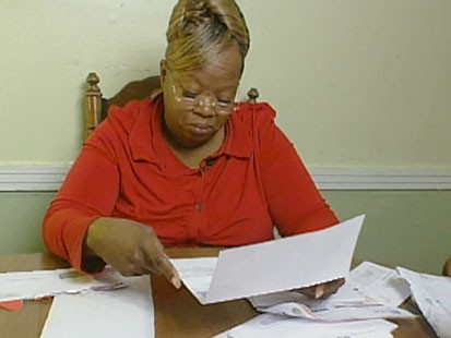 A picture of Lizzie Revels looking at her bills.