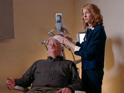 A picture of a man undergoing transcranial magnetic stimulation.