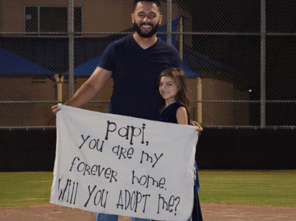 PHOTO: Leonardo Avila stood on a pitchers mound at a baseball field in Alabaster, Alabama on Sept. 21. When he opened his eyes, his stepdaughter Alessandra was holding a sign asking him to make her his own.