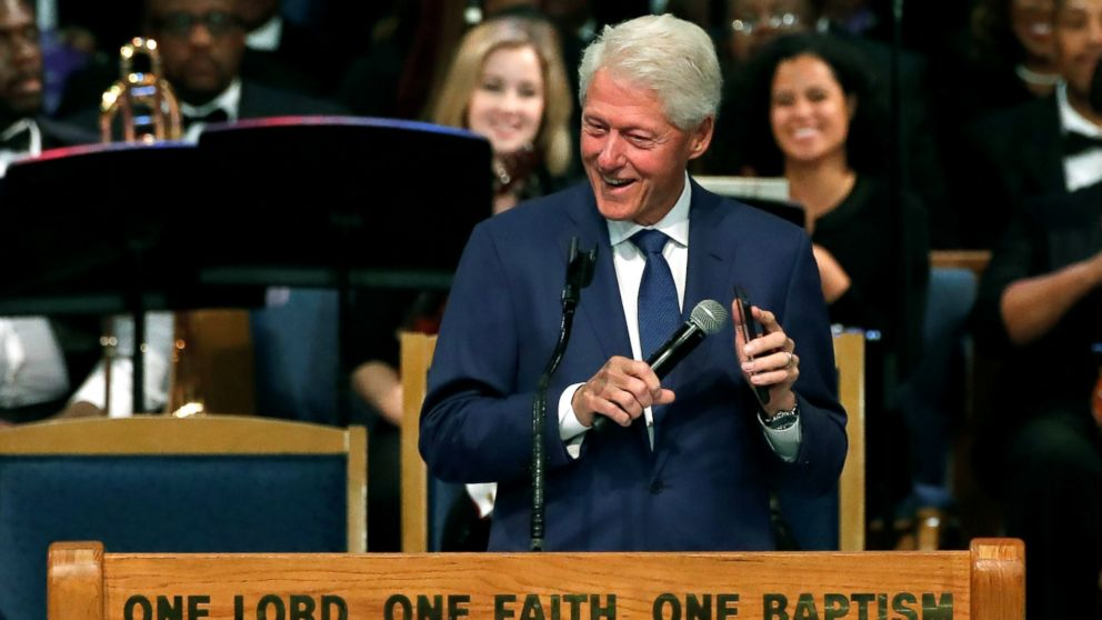 Former President Bill Clinton plays Aretha Franklin music on his mobile phone while speaking at the funeral service for the late singer at the Greater Grace Temple in Detroit, Aug. 31, 2018.