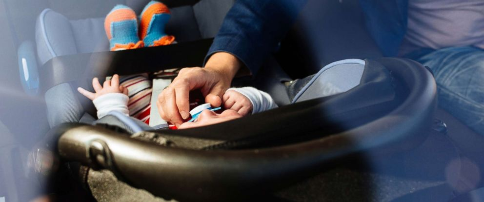 PHOTO: In this undated stock photo, a mother puts her baby in a rear facing car set.
