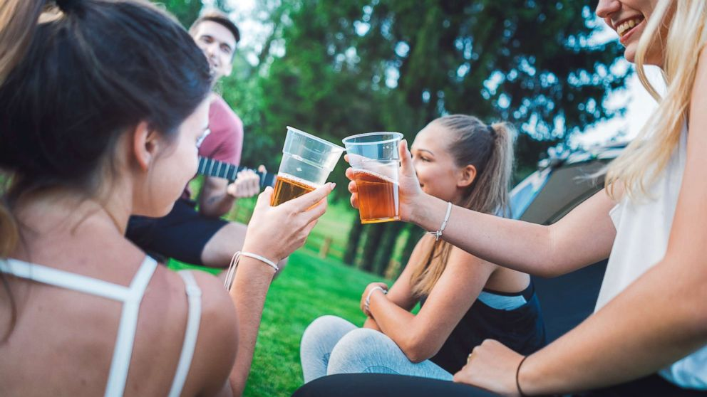 Young people drink beer outdoors in an undated stock photo.