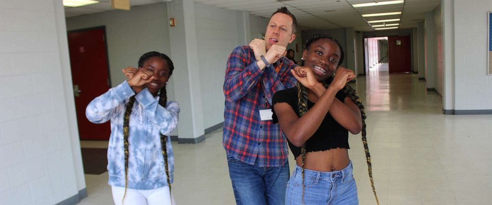 PHOTO: Dr. Trevor Boffone, a Spanish teacher at Bellaire High School in Bellaire, Texas, dances with his students, Takia and Talia Palmer.
