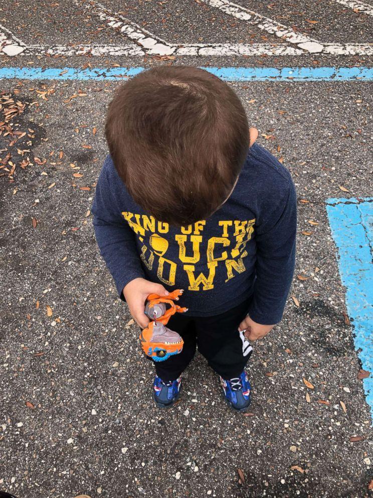 PHOTO: Jordan holds his broken dinosaur toy outside Best Buy.
