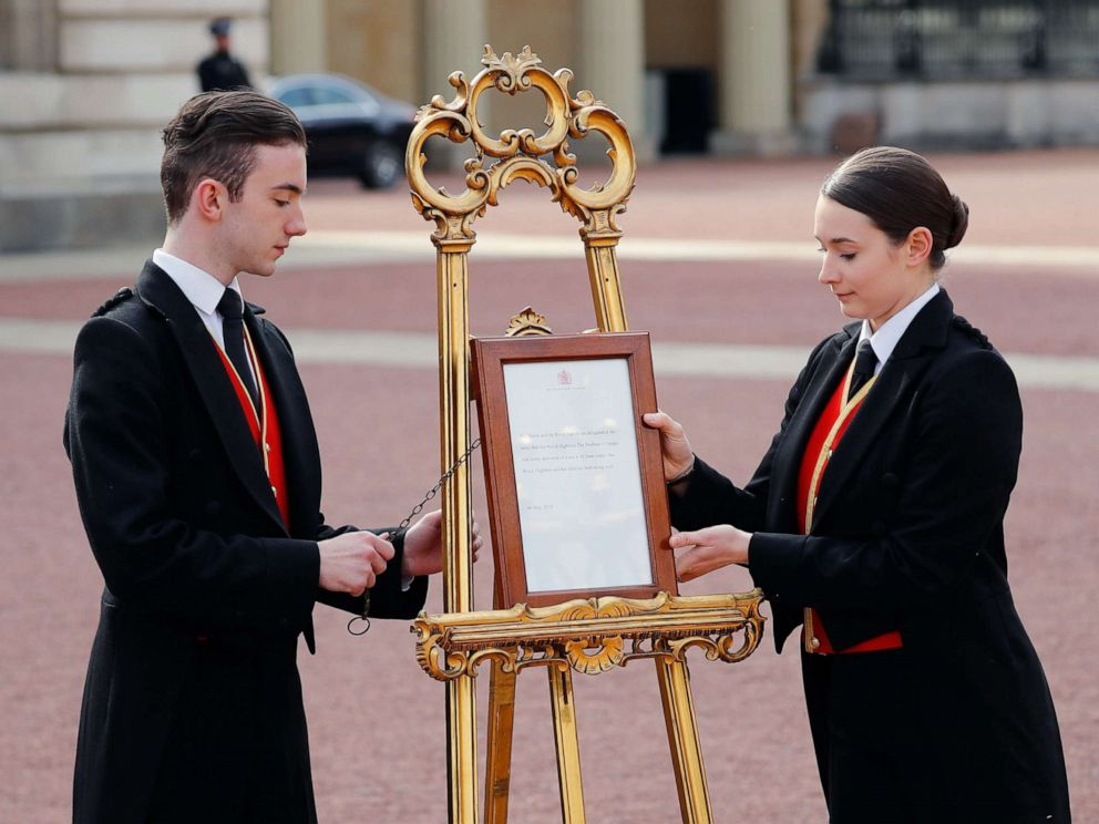 PHOTO: Members of staff set up an official notice on an easel at the gates of Buckingham Palace in London on May 6, 2019 announcing the birth of a son to Britains Prince Harry, Duke of Sussex and Meghan, Duchess of Sussex.