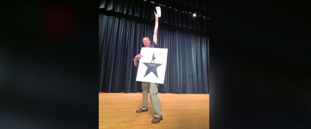 "PHOTO: Tom Corby poses with a card from his students after they surprised him with tickets to see the musical ""Hamilton."""