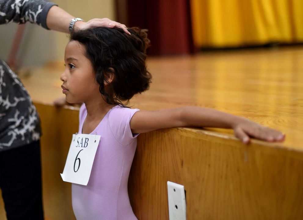 PHOTO: Six-year-old ballet dancer Charlotte Nebres prepares for auditioning as boys and girls ages 6 to 7 try out for The School of American Ballet Winter Term at the P.S. 124 Yung Wing school in New York, April 16, 2015.