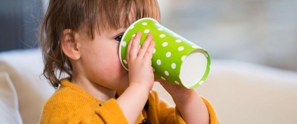 PHOTO: Young toddler drinking from a disposable cup.