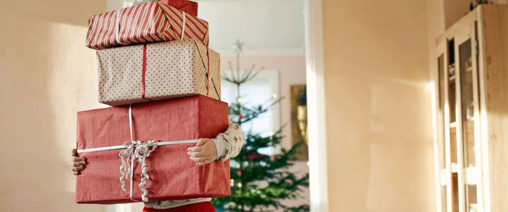 PHOTO: A young child carrying Christmas presents is depicted in this stock photo.