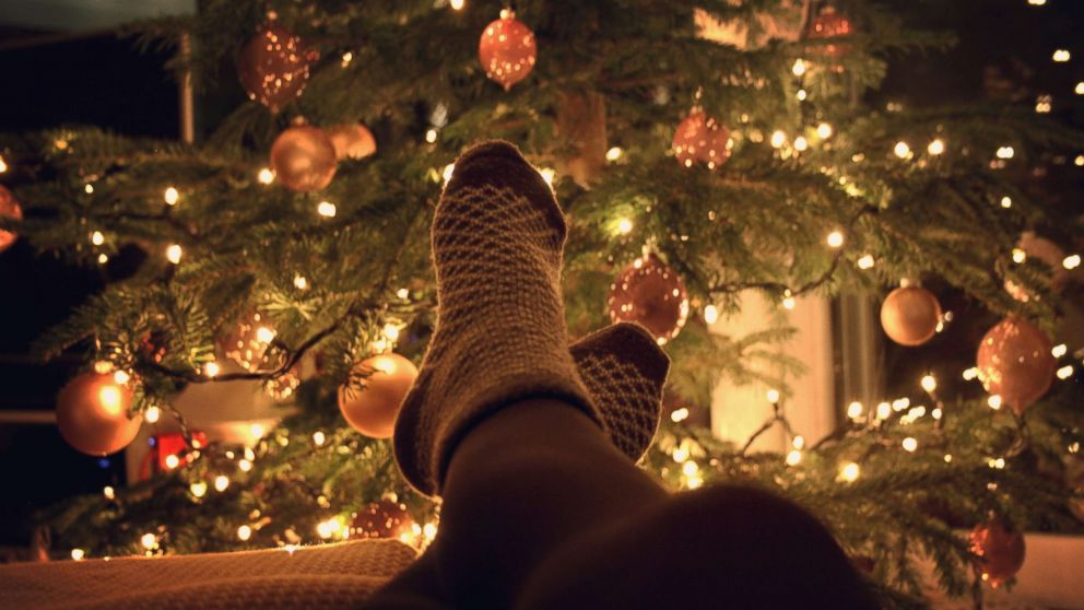 A person rests near a Christmas tree in an undated stock photo.