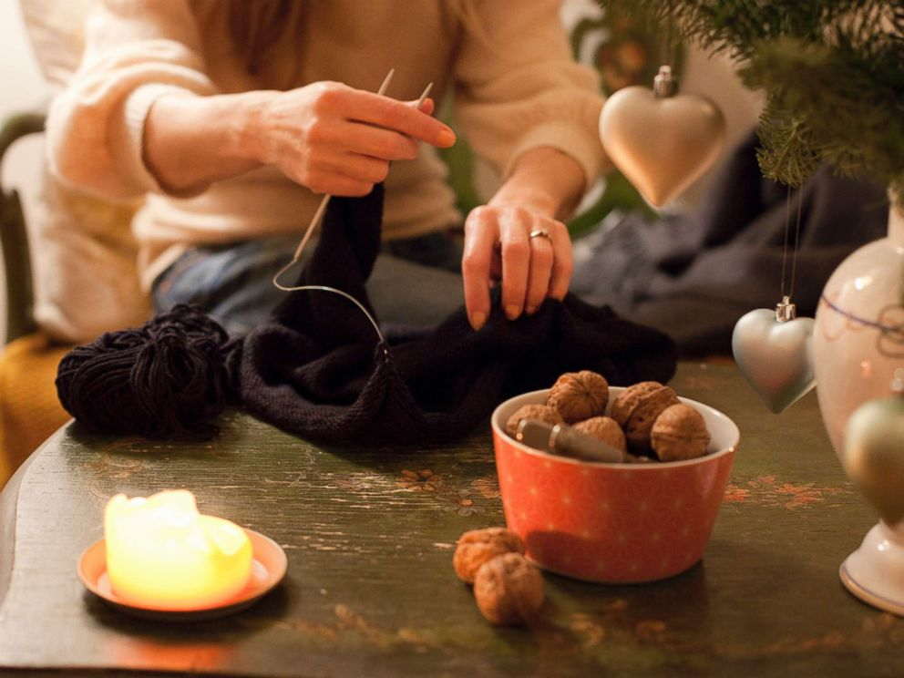 PHOTO: A woman knits by a Christmas tree in an undated stock photo.
