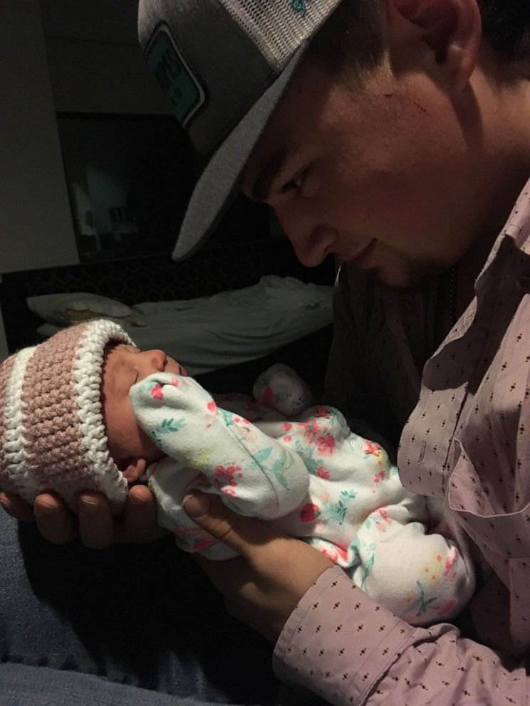 Dad nestles his newborn daughter on top of his guitar to