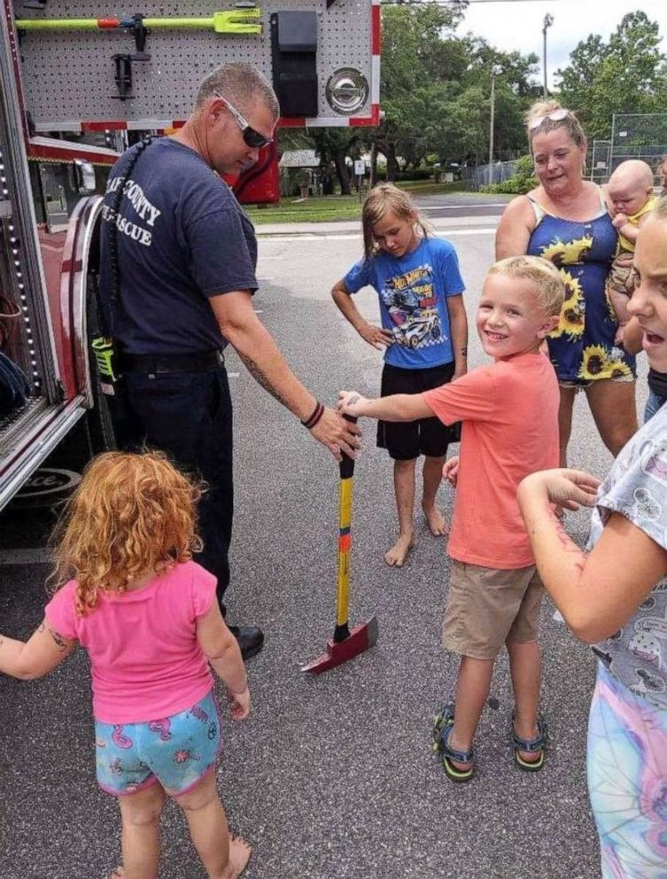 PHOTO: Colten Raymer and his new friends are shown having fun with the firefighters and fire truck.