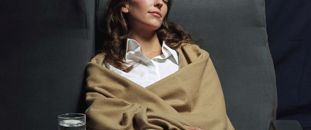 PHOTO: A stock photo depicts a woman relaxing comfortably on an airplane.