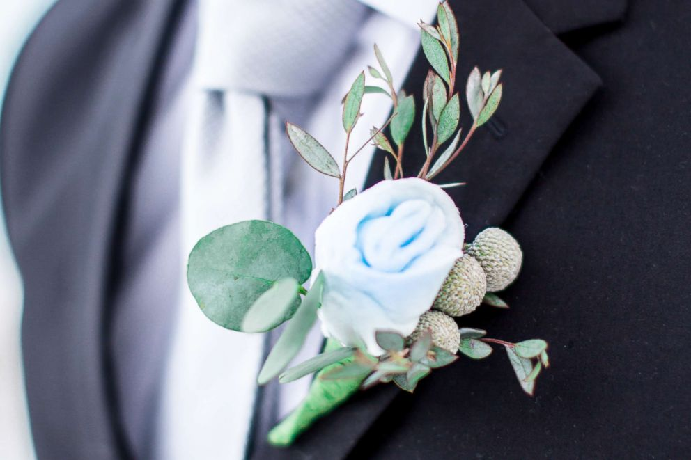 A model displays a boutonniere flower crafted from cotton candy in a wedding-style photo shoot by Milwaukee-based wedding photographer Lottie Lillian.