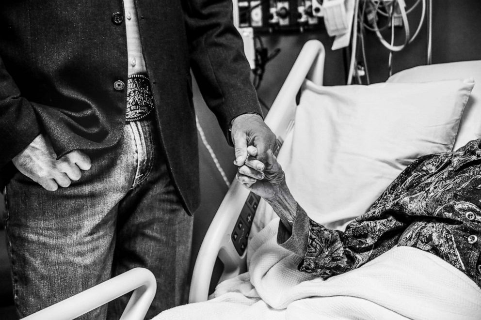 PHOTO: Clay Cameron holds the hand of his grandmother, Charlotte Bussard, 100, at Hemphill County Hospital in Hemphill County, Texas, in May 2019.