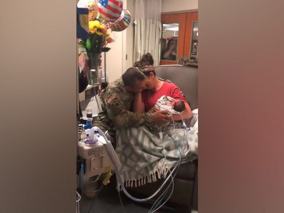 PHOTO: Skyler Cooper, a member of the Kansas Army National Guard, surprises his wife, Cydney Cooper of Topeka, Kansas and their newborn twins, Emma and Kyla Cooper.
