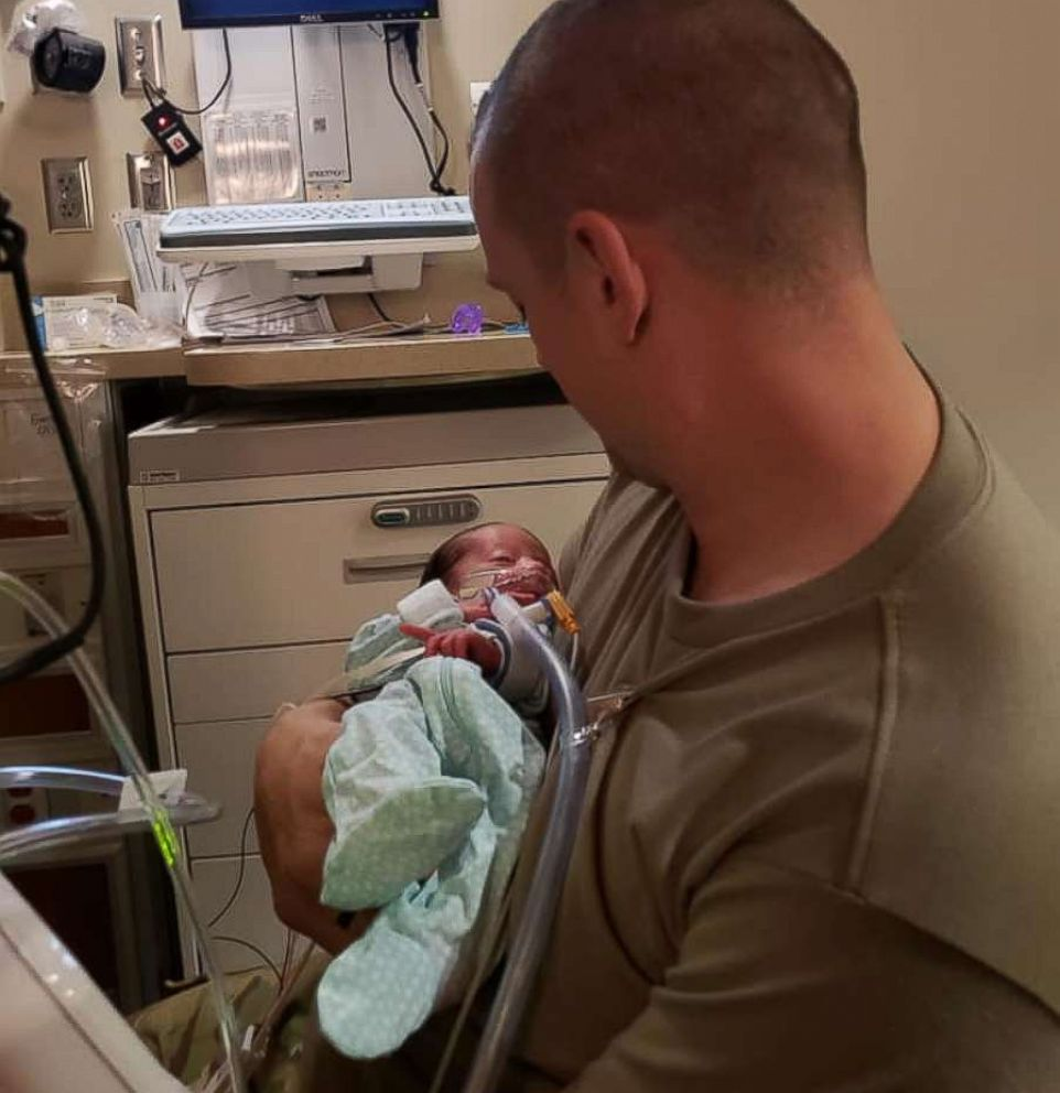 PHOTO: Skyler Cooper, a member of the Kansas Army National Guard, holds his newborn daughter, Emma Cooper, on Feb. 4.