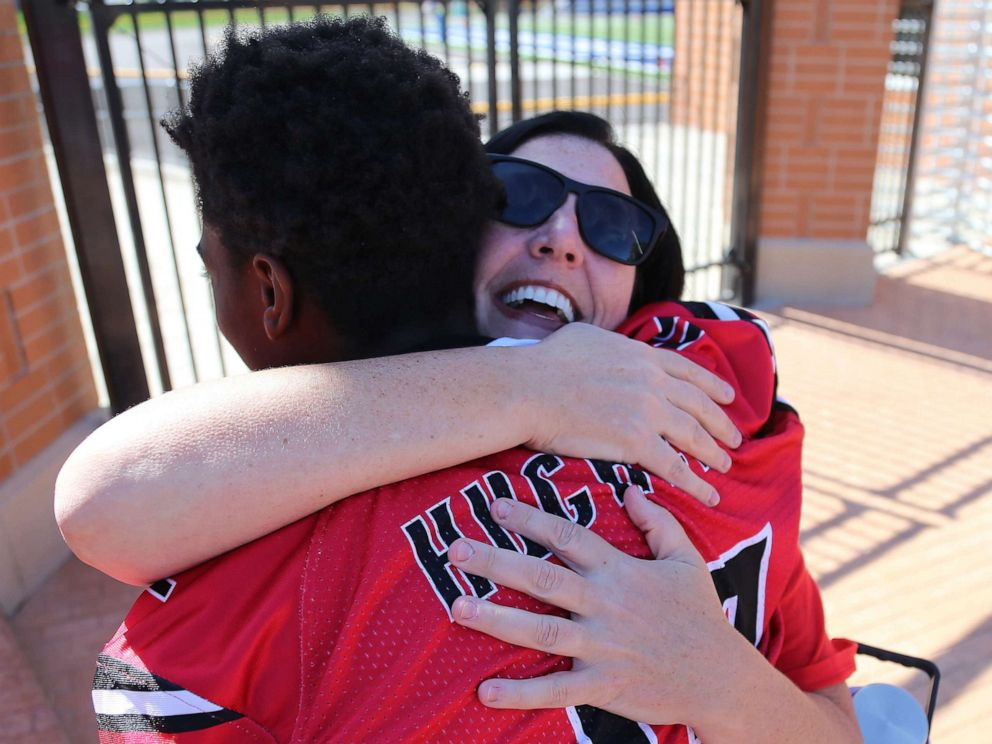 PHOTO: Dana Gendreau hugs the Hughes football player as they get off the bus before there game on Oct. 6, 2019.