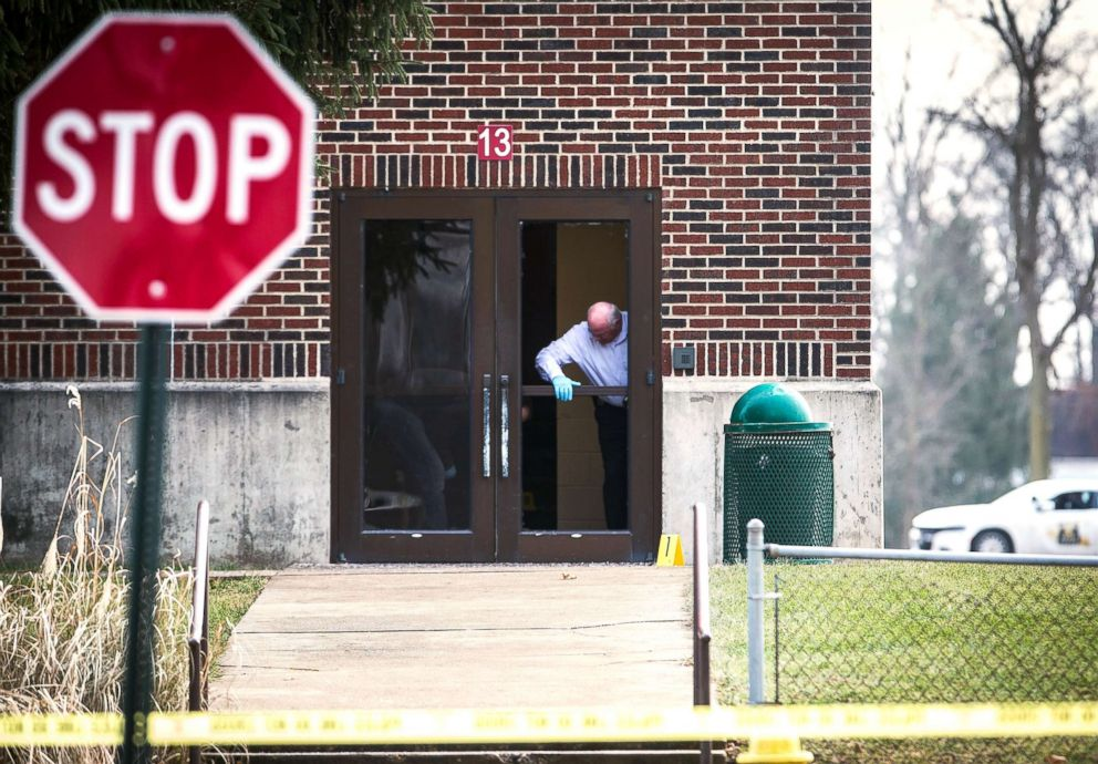 PHOTO: Investigators examine a a door at Dennis Intermediate School where a shooter allegedly broke the glass to enter the building in Richmond, Ind., Dec. 13, 2018.