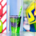 Disney's Space Ranger Slush conains layers of purple grape and green apple slush with a green rock candy straw.