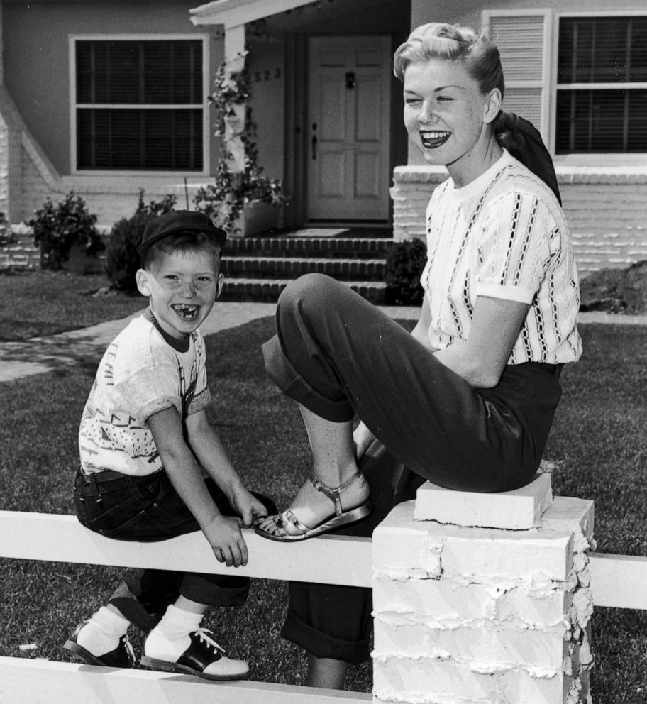 PHOTO: American actress and singer Doris Day sits on a fence in front of a house with her son, Terry.