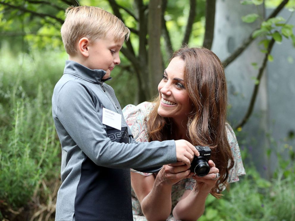 PHOTO: Catherine, Duchess of Cambridge speaks with Josh Evans at photography workshop for Action for Children, run by the Royal Photographic Society at Warren Park on June 25, 2019, in Kingston, England.