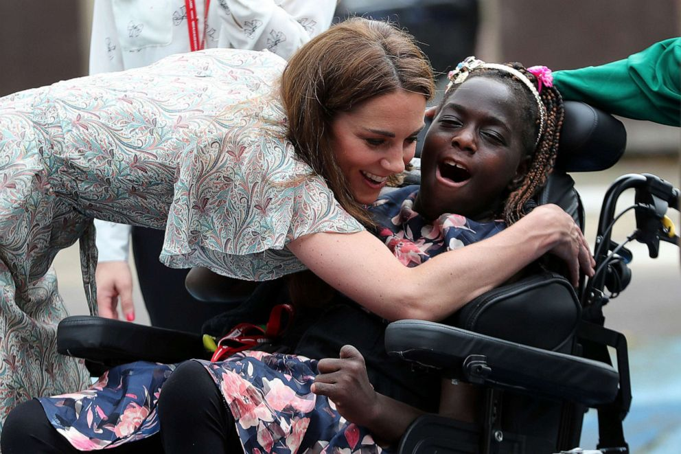 PHOTO: Britains Kate, Duchess of Cambridge hugs Faith Olukoya at a photography workshop for Action for Children, run by the Royal Photographic Society in Kingston, England, June 25, 2019.