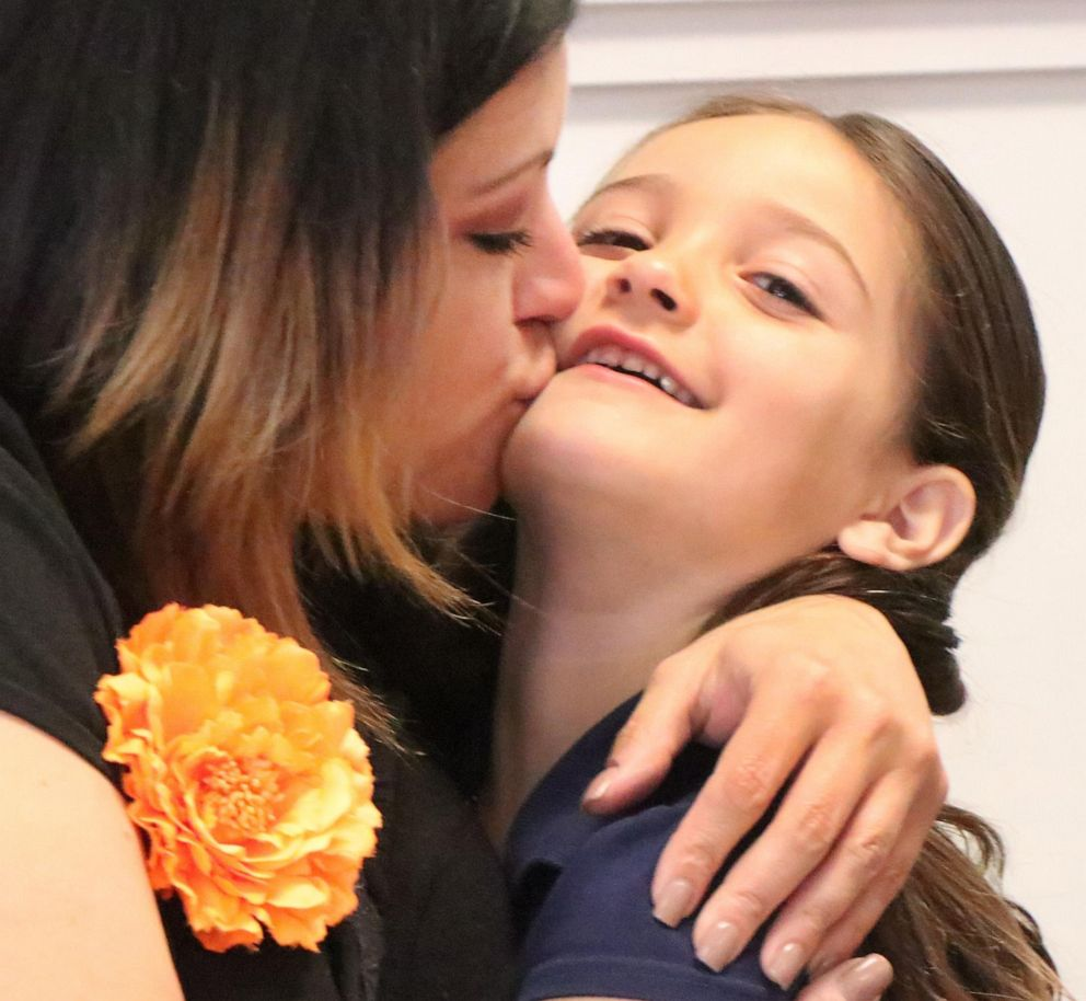 PHOTO: Nicole Chapman gives daughter Eva Chapman a big hug and kiss, Monday May 13, 2019, the six year old Spruce Creek Elementary kindergartener has collected a hundred or more jars of peanut butter and jelly for a food drive.