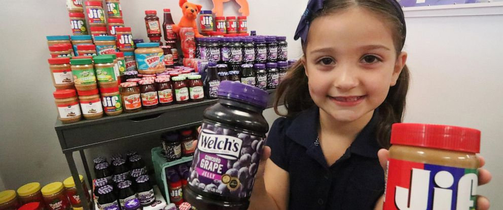 PHOTO: Eva Chapman, a six year old Spruce Creek Elementary kindergartener, holds a couple of the hundred or more jars of peanut butter and jelly she collected for a food drive, May 13, 2019 so kids won't go hungry over the summer.