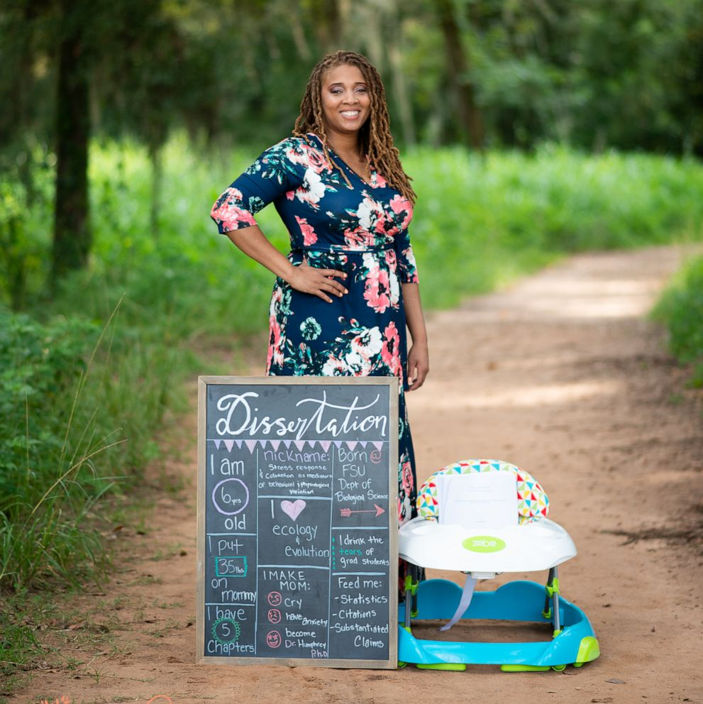 PHOTO: Eve Humphrey poses with her dissertation in a newborn photoshoot spoof after she completed her doctorate in biology at Florida State University in fall 2019.