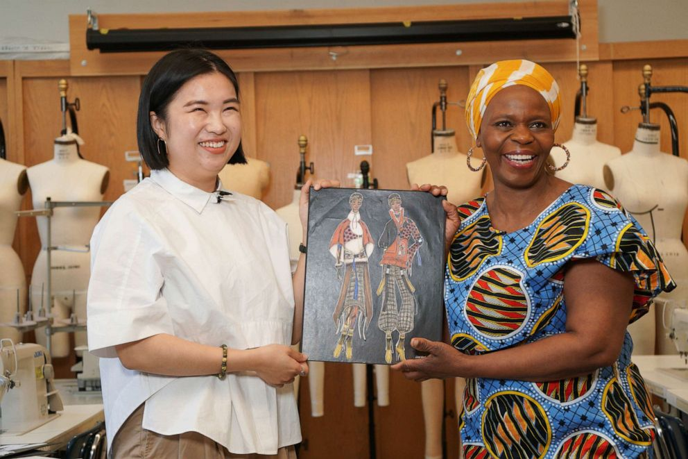 PHOTO: Eunhye Jo (FIT student) and Tshidi Manye (Rafiki The Lion King) review design sketches for Rafiki inspired garments.