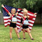 Avery Braden, left, and Tatum Daub, hold an American flag in their Halloween costumes as Shalane Flanagan.
