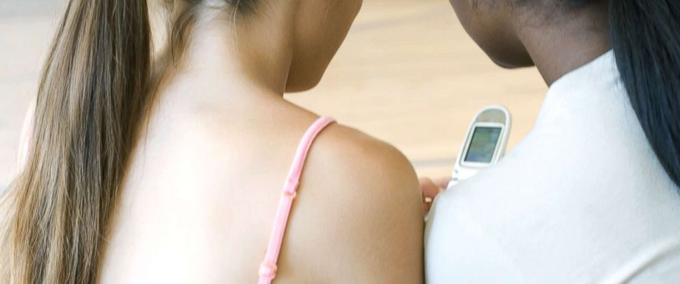 PHOTO: A stock photo of two girls with a flip phone.