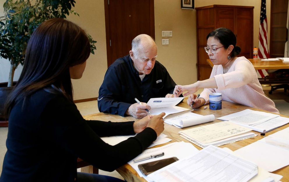 PHOTO: Gov. Jerry Brown reviews a measure with staff members Camille Wagner, left, Graciela Castillo-Krings at his Capitol office, Sept. 30, 2018, in Sacramento, Calif.