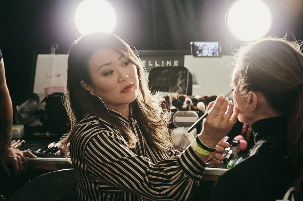 PHOTO: Grace Lee applying makeup on a model backstage at Rebecca Minkoff.