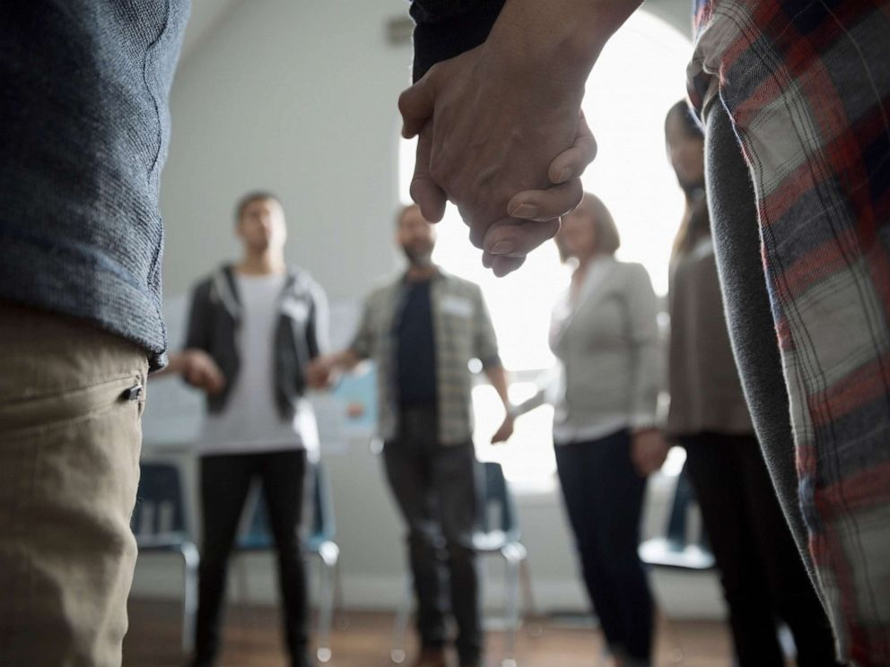 PHOTO: An undated stock photo shows a group of people holding hands in a circle.