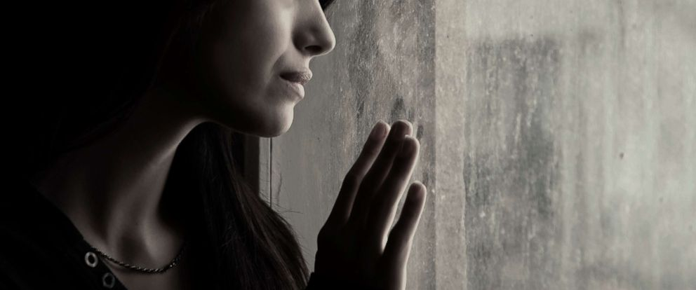 PHOTO: A stock photo depicts a woman looking out a window.