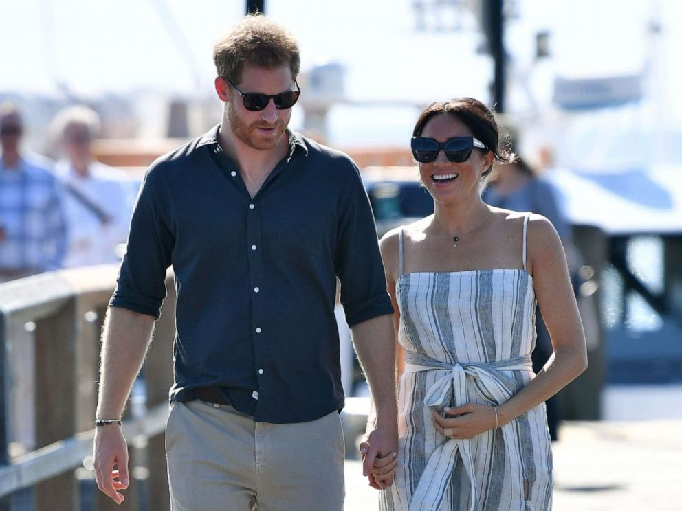 PHOTO: Britains Prince Harry and his wife Meghan, the Duchess of Sussex walk to attend a meet-the-people session at Kingfisher Bay Resort on Fraser Island, Oct. 22, 2018.