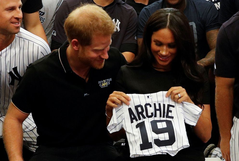 PHOTO: Prince Harry, Duke of Sussex, and his wife Meghan, Duchess of Sussex are presented with gifts for their son Archie, as they meet New York Yankees players before their match against the Boston Red Sox at the London Stadium, June 29, 2019.