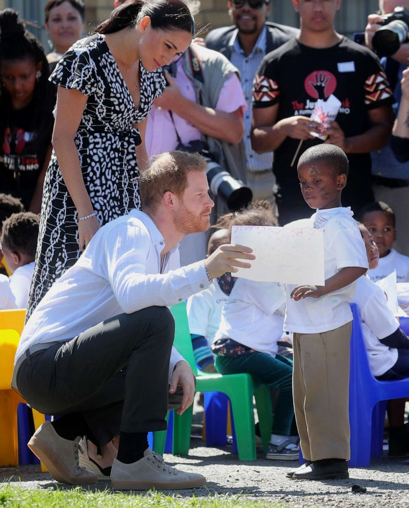 PHOTO: Meghan, Duchess of Sussex and Prince Harry, Duke of Sussex talk with a young boy during a visit to a Justice Desk initiative in Nyanga township, during their royal tour of South Africa, Sept. 23, 2019 in Cape Town.