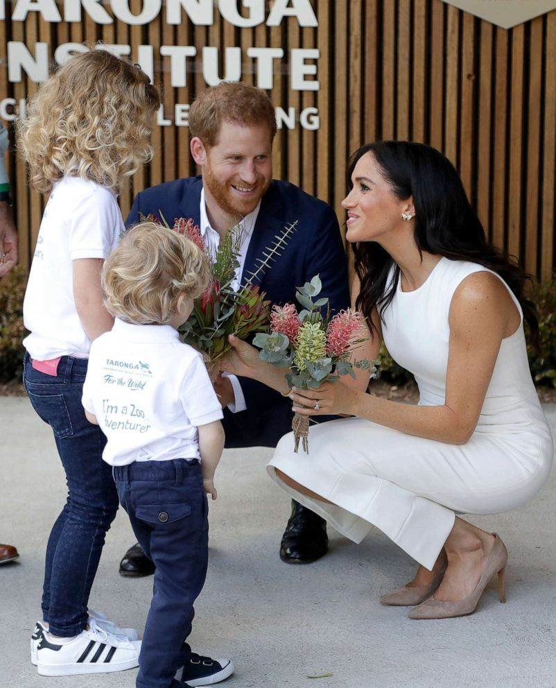 Prince Harry, Duke of Sussex and Meghan, Duchess of Sussex are presented with native flowers from children, Dasha Gallagher and Finley Blue, during a ceremony at Taronga Zoo, Oct. 16, 2018, in Sydney.