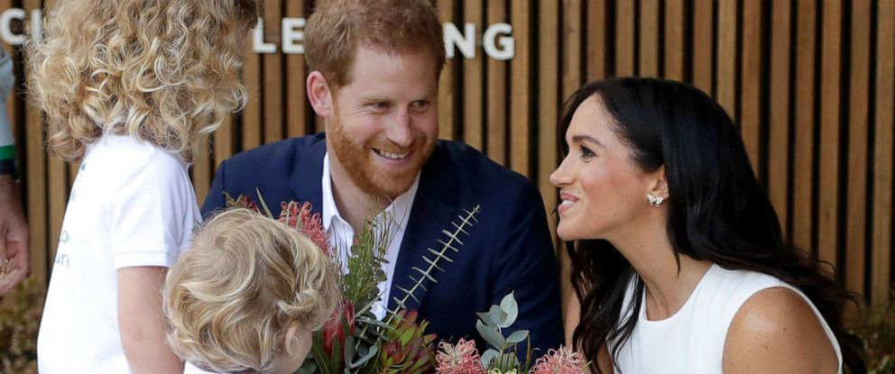 PHOTO: Prince Harry, Duke of Sussex and Meghan, Duchess of Sussex are presented with native flowers from children, Dasha Gallagher and Finley Blue, during a ceremony at Taronga Zoo, Oct. 16, 2018, in Sydney.