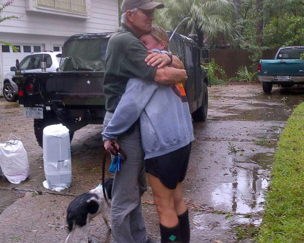 Jane Henry hugs her father after Hurricane Harvey destroyed her home.