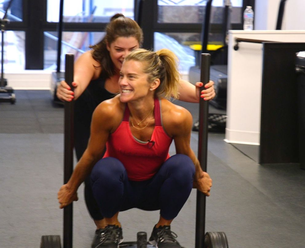 PHOTO: Holly Rilinger, creator of LIFTED, is pushed on a power sled by Julia Dodds.