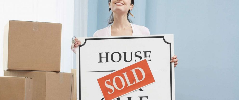 "PHOTO: An undated stock photo depicts a woman holding a ""sold"" sign in a new home."